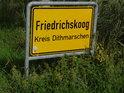 Místní cedule Friedrichskoog je poněkud utopena v příkopě a trávě.